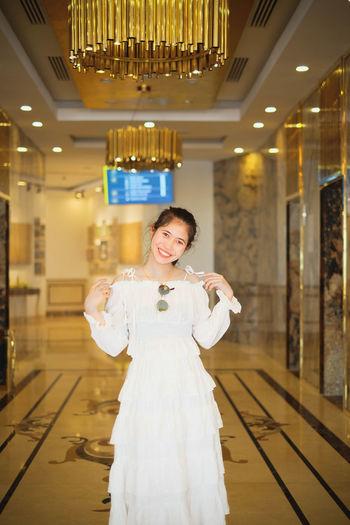 Portrait of smiling woman standing in corridor
