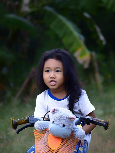 Cute girl looking away while riding bicycle in park