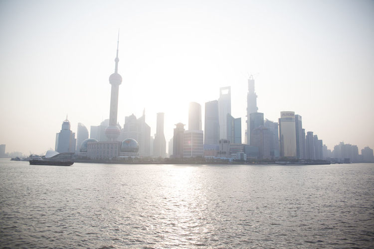 Huangpu River In Front Of Oriental Pearl Tower Amidst Buildings In City Against Clear Sky