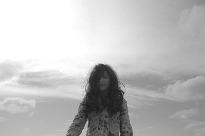 Portrait of young woman standing against sky