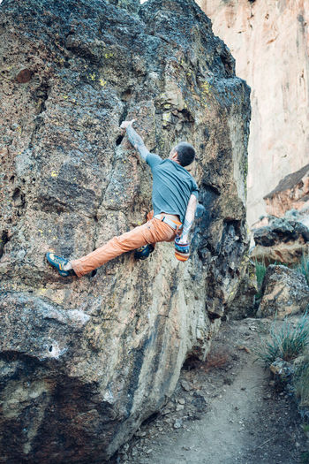 Full length of man climbing on rock
