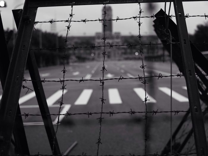 A barbed wire gate blocks entrance to a parade ground