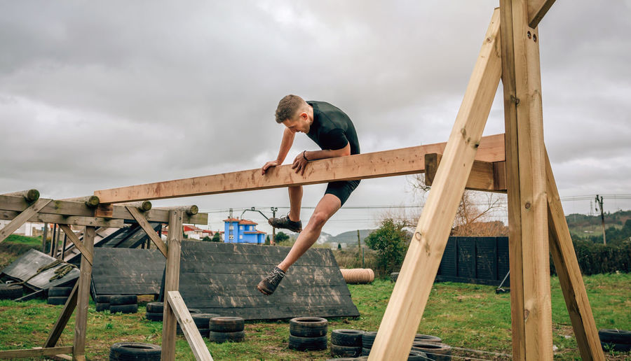 Man jumping on wood against sky