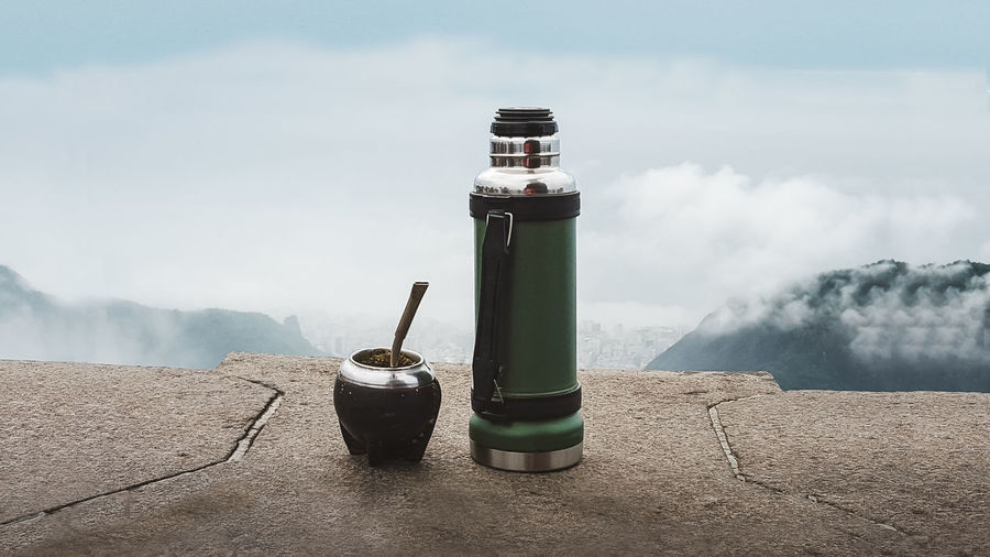 Close-up of water bottle on mountain against sky