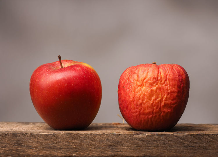 Two red apples on a table Agriculture Concepts Freshness New Red Rustic Apples Conceptual Delicious Food Fresh Fruits Healthy Eating Metaphor Old Skin Skincare Table Two Wrinkled Skin Young Adult