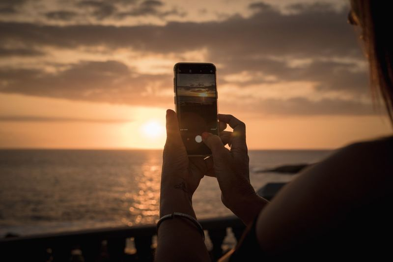 Sunset passion Sunset Sunset_collection Communication Portable Information Device Smart Phone Hand Cloud - Sky Nature Real People Mobile Phone Holding Leisure Activity One Person Human Hand Activity