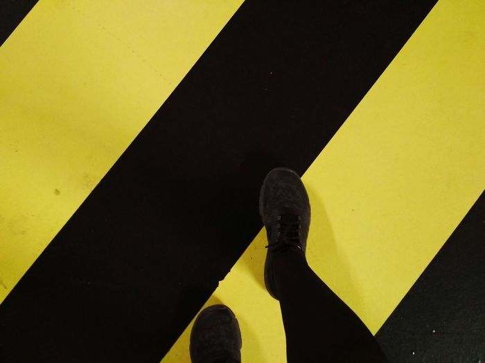 Low section of person standing on yellow road sign