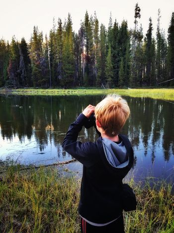 Birdwatching Water Lake Tree Lakeshore Leisure Activity Lifestyles Non-urban Scene Tranquil Scene Reflection Fishing Rod Casual Clothing Tranquility Holding Standing Green Color Nature Beauty In Nature Scenics Person Tourism My Son ❤ Bird Watching