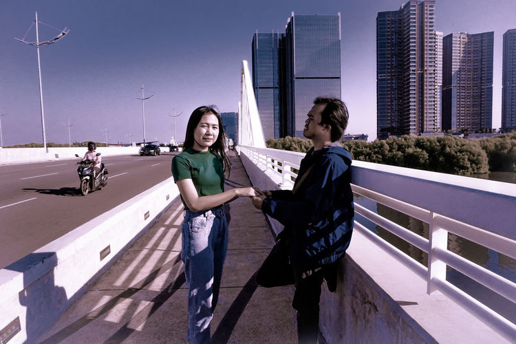 Man and woman on bridge holding each other