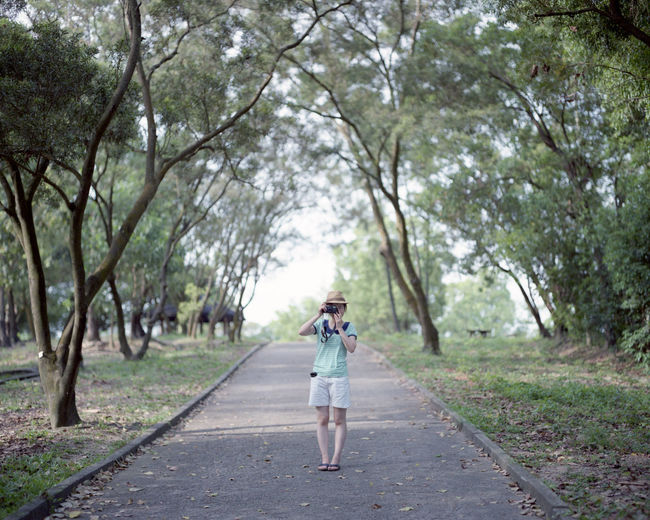 Woman photographing amidst trees on footpath at park