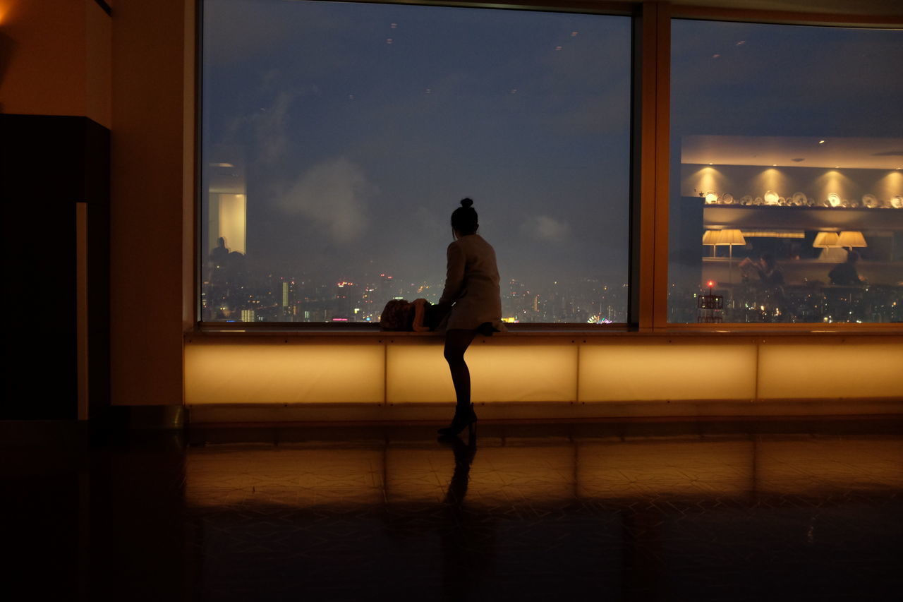 Rear view of woman sitting at window during night
