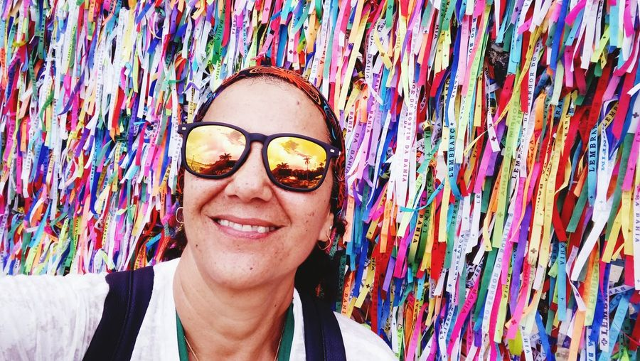 Portrait of smiling woman wearing sunglasses against multi colored bands