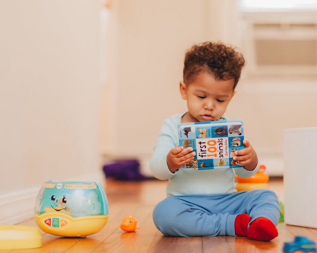 Cute boy holding toy while sitting on floor at home