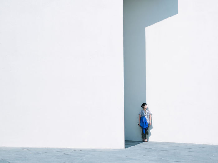 Man standing against white wall