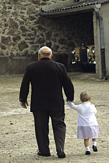An Old Man And A Small Child Day Going To A Fest Grandfarther And A Child Holding Hands And Walking Outdoors Senior Adult Toghetherness Two People