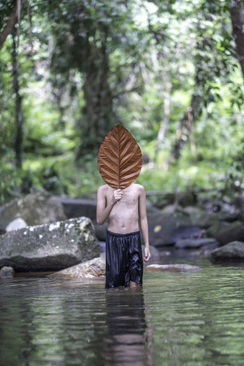 Shirtless man holding leaf while standing in lake against trees