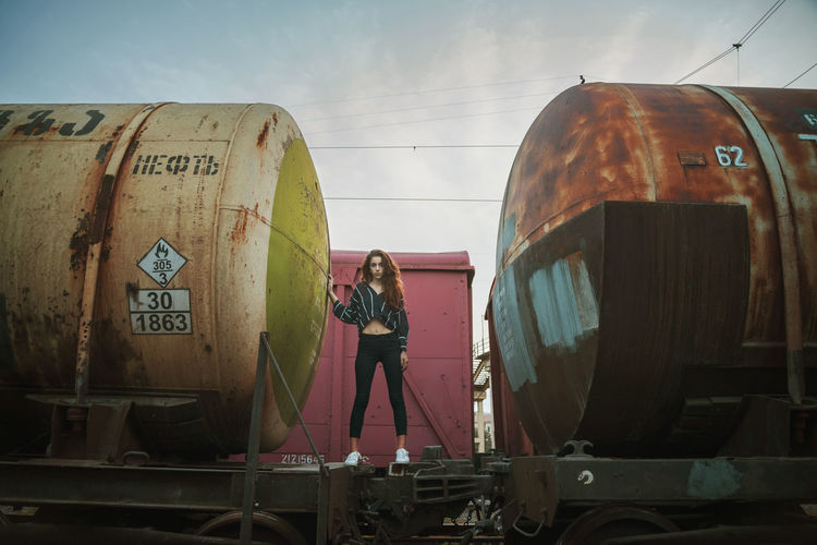 Young woman standing on abandoned freight train