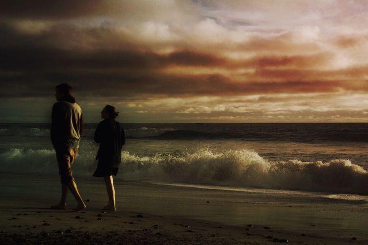 People walking on beach at sunset