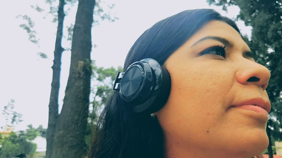 Close-up of woman listening music on headphones against trees