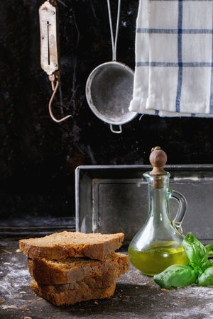 Sliced homemade rye bread, battle of olive oil and fresh basil over kitchen table powdered with flour, with towel, bread pan and vintage stainer and steelyard at background Basil Black Bottle Bread Dark Photography Flour Foodphotography Fresh Baked Homemade Bread Kitchen Kitchen Utensil Olive Oil Rye Bread Sandwich Sliced Bread Wholegrain
