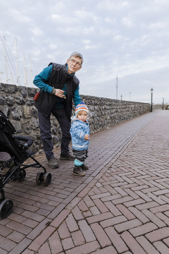 Man with toddler girl on sidewalk – Hindeloopen, Netherlands, Europe Attention Baby Care Man Netherlands Road Standing Traffic Waiting Wall Baby Stroller Child Childhood Full Length Holding Mature Adult Mature Men Outdoors Pavement Safety Serious Street Toddler  Two People Watching
