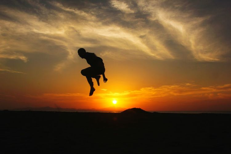 Silhouette man jumping against orange sky during sunset