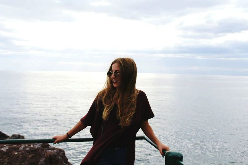 Young woman leaning on railing against sea