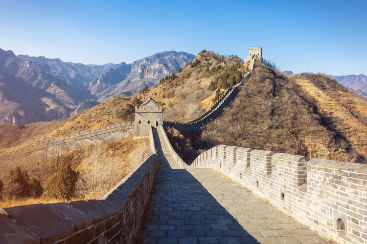 Ancient Civilization Stone Wall Outdoors Fort Mountain Range Staircase Building Exterior Sunlight No People Ancient Scenics - Nature Day Tourism Surrounding Wall Travel Sky Wall Nature History The Past Travel Destinations Mountain Built Structure Architecture Great Wall Of China