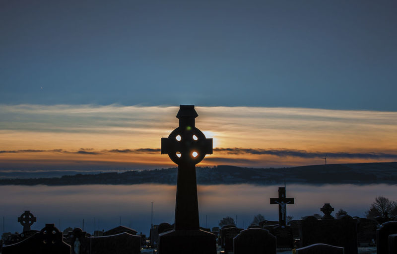 Cross and tombstones in graveyard against sky during sunset