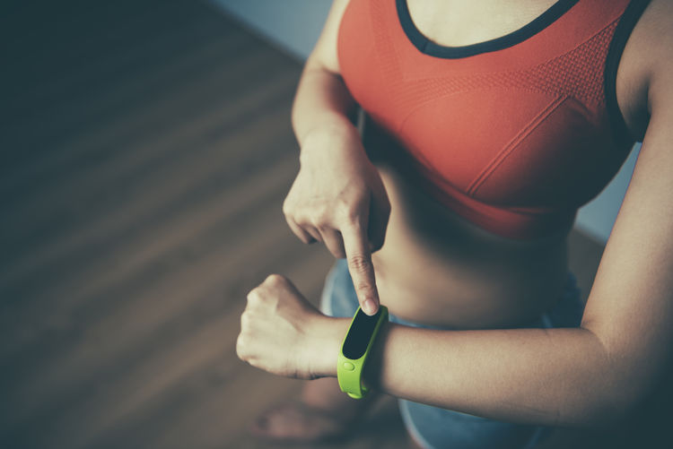 Adult Athlete Body Conscious Close-up Exercising Fit Fitness Focus On Foreground Hand Healthy Lifestyle Holding Human Body Part Human Hand Leisure Activity Lifestyles Midsection One Person Real People Smart Watch Sport Sports Clothing Stopwatch Strength Timer Women