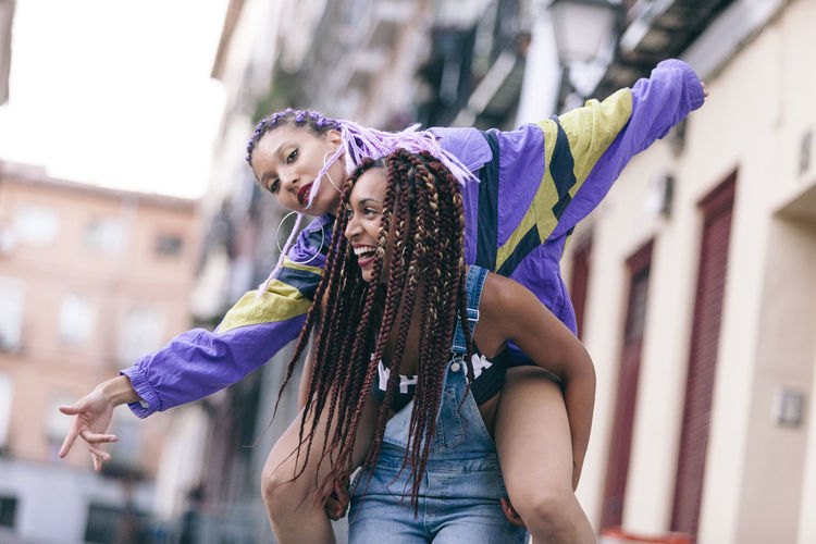 Low angle view of happy woman piggybacking female friend in city