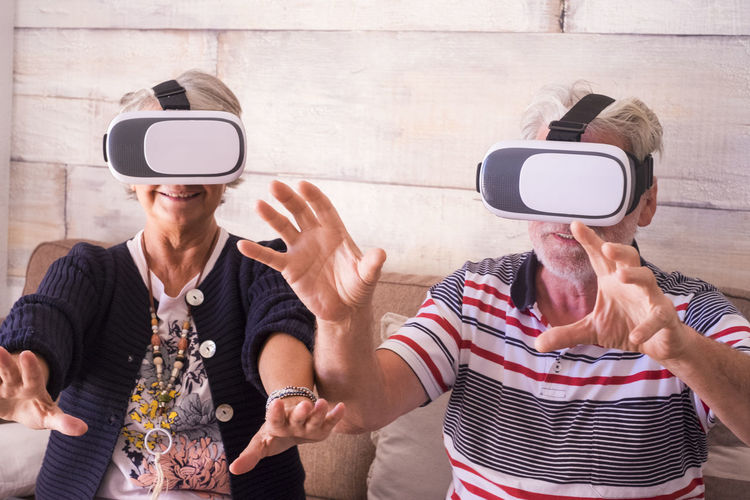 Senior couple wearing virtual reality simulator against wall