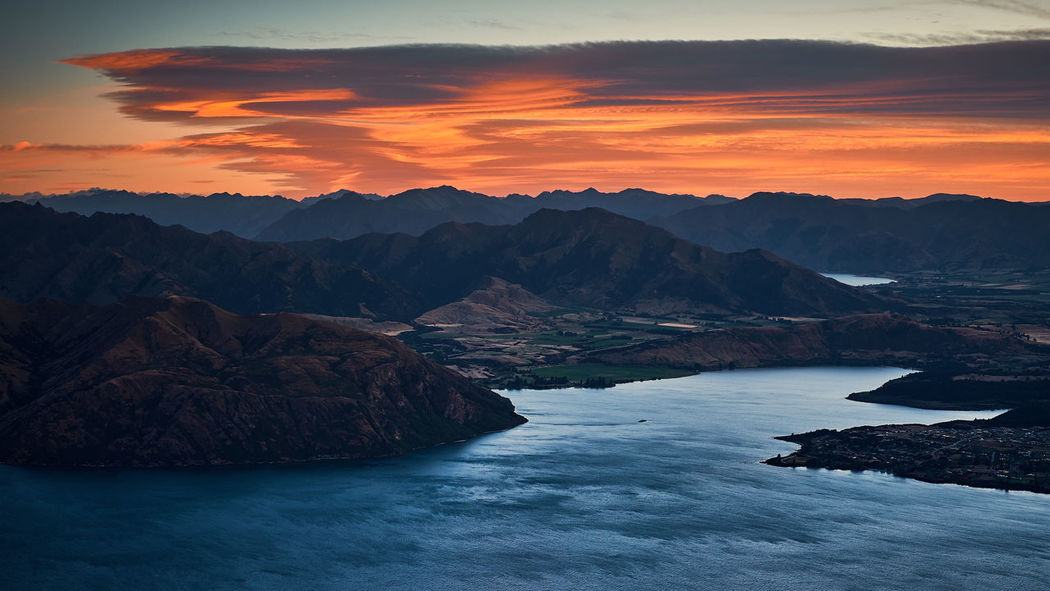 Sunrise over Lake Wanaka, South Island of New Zealand Beauty In Nature Cloud - Sky Eroded Idyllic Lake Wanaka Mountain Mountain Range Nature New Zealand No People Non-urban Scene Orange Color Outdoors Rock Rock - Object Roys Peak Scenics - Nature Sky Solid Sunrise Sunset Tranquil Scene Tranquility Water Waterfront