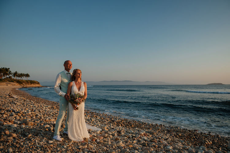 Bride and groom standing on beach against clear sky