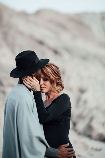 Couple embracing while standing at desert