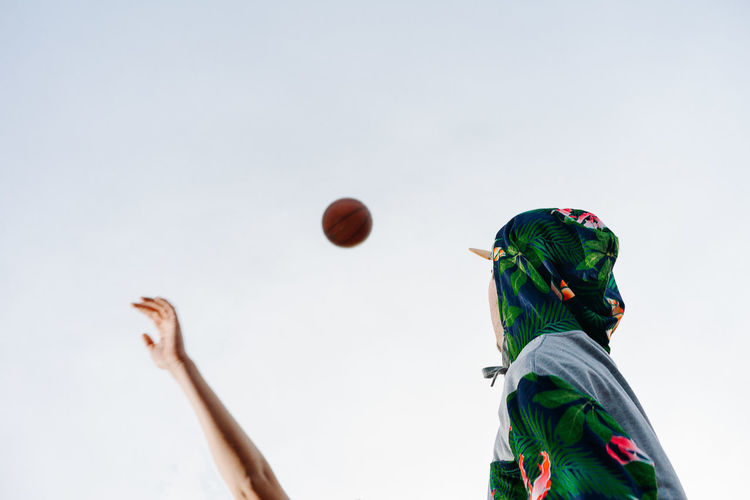Low angle view of man looking at basketball in mid-air against clear sky