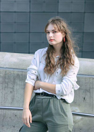 Portrait of beautiful young woman standing against wall