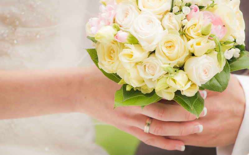 Cropped Image Of Newly Wed Couple Holding Flower Bouquet