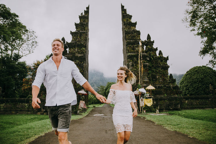 Couple running on footpath at gate against sky