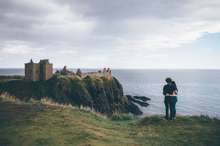 Rear view of couple standing by dunnottar castle against cloudy sky