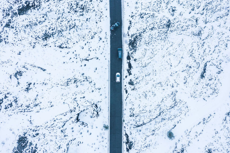 Aerial view of road amidst snow covered fields