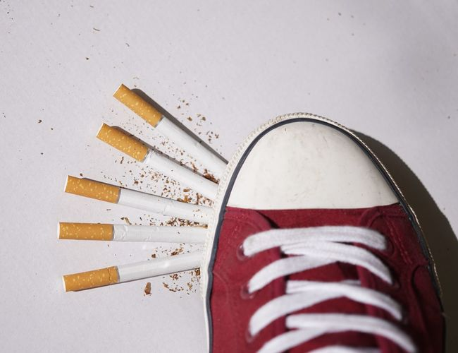 Close-Up Of Canvas Shoe On Cigarettes