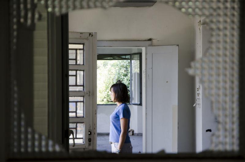 Side view of woman seen through broken window