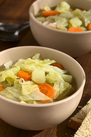 Savoy cabbage, carrot and potato stew or thick soup in bowls with slices of bread on the side, photographed on dark wood with natural light (Selective Focus, Focus in the middle of the first dish) Diet Homemade Homemade Food Potato Vegetarian Bowl Cabbage Carrot Cooked Cruciferous Food Food And Drink Fresh Healthy Healthy Eating Hotpot Meal Ready-to-eat Savoy Cabbage Soup Stew Vegan Vegan Food Vegetable Vegetarian Food