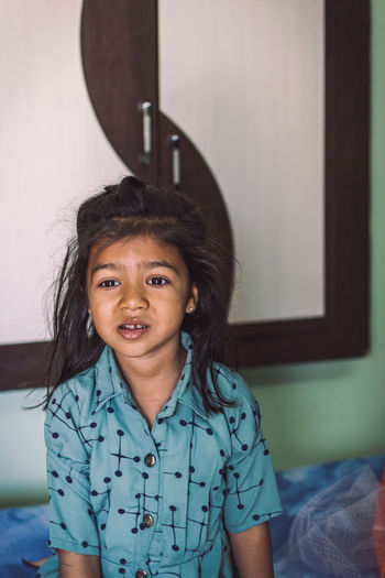 Portrait of cute girl sitting on bed at home