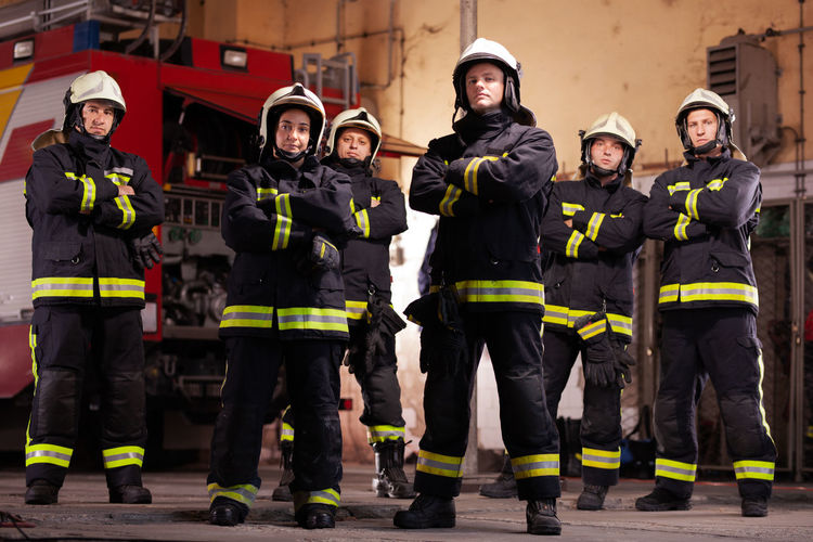 Portrait of firefighters standing in fire station