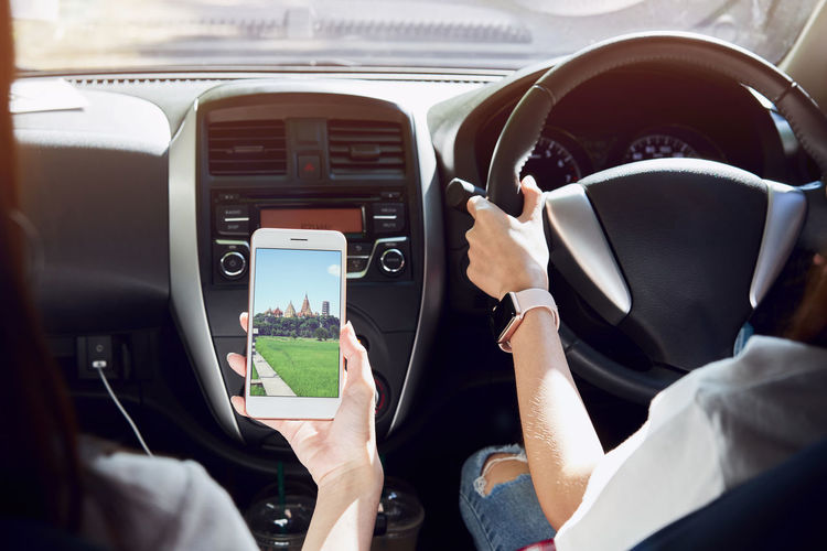 women is driving car. rear view can look to the front in same view as driver. And friends are holding smartphone on picture of the scenery to the destination. Technology Mode Of Transportation Wireless Technology Real People Men Communication Transportation Human Hand One Person Human Body Part Mobile Phone Hand Land Vehicle Smart Phone Screen Car Vehicle Interior Travel Lifestyles Outdoors