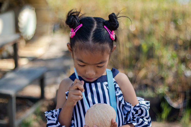 Close-up of cute girl drinking coconut