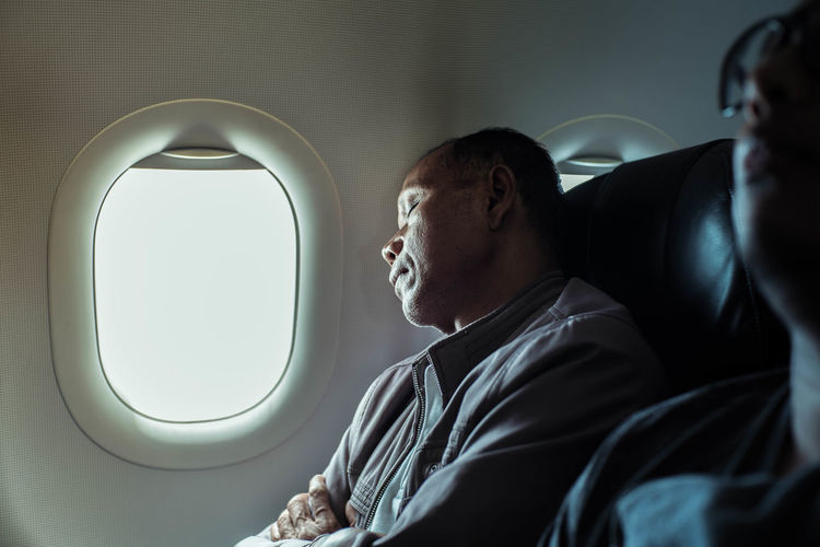Mature man sleeping while sitting in airplane