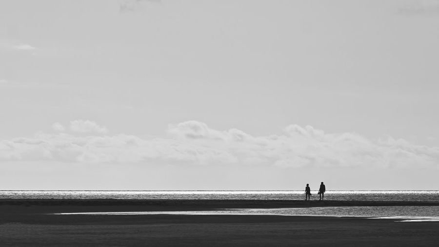 Silhouette people standing on beach against sky